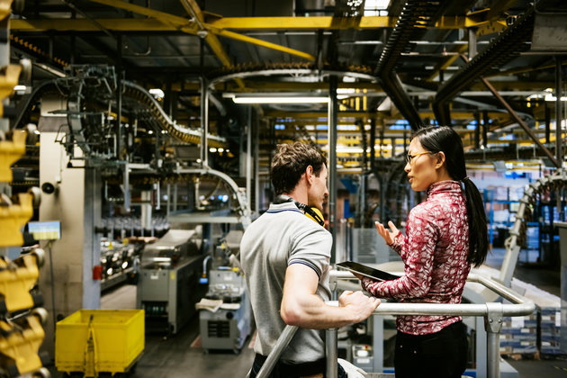 Mechanic and manager talking nearby a machine in a big printery about latest newspaper print TOMML VIA GETTY IMAGES