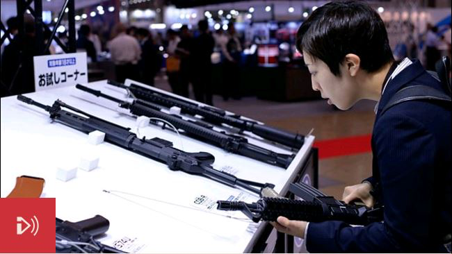 Photo: A man handles a fake gun on show at the Japan Models and Hobby Show 2016. Credit: Getty Images